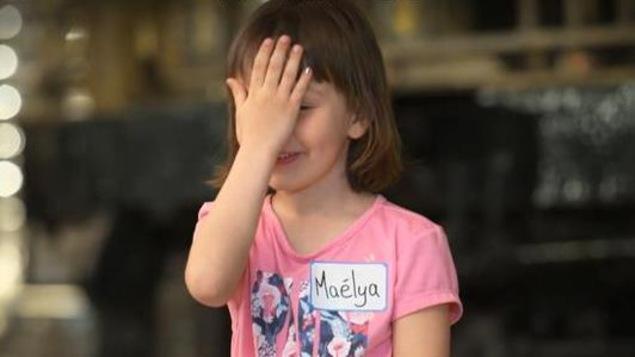 Une petite fille met sa main sur son front.