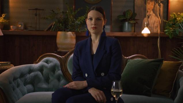 La jeune femme est assise dans un canapé, l'air sérieux, avec les cheveux tirés vers l'arrière.