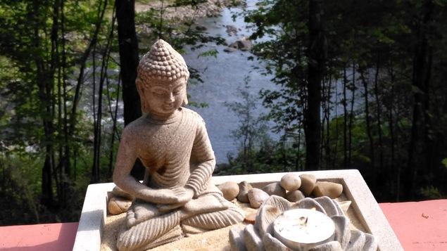 Une statuette dans un bac de sable qui contient des pierres et une chandelle dans une fleur de lotus est installé sur un balcon avec vue sur la rivière.