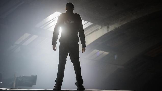 """Un homme avec une veste """"POLICE"""" se tient debout dans un entrepôt sombre"""