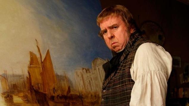 Un homme en gilet et chemise à jabot devant une peinture.
