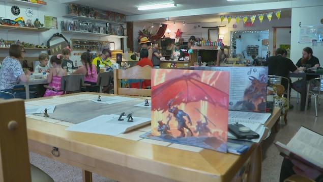 Plusieurs tables avec des gens, petits et grands, qui font des activités.