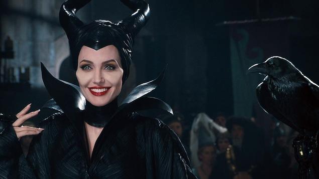 Une femme souriante, toute en noir, avec des cornes sur la tête et un corbeau à sa droite.