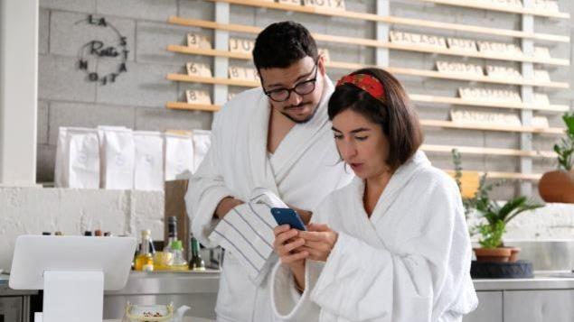 Deux personnes en robe de chambre dans un café regardent un téléphone cellulaire.