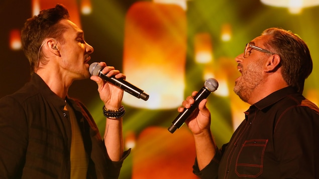 Les deux chanteurs se regardent, micro à la main, interprétant une chanson en duo.