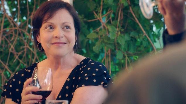 Elle sourit et tient une coupe de vin rouge.