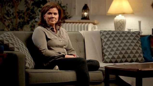 Elle est assise sur un canapé dans une pièce à éclairage tamisé.