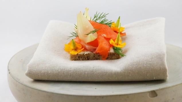 Pain avec du saumon fumé et des petites fleurs.