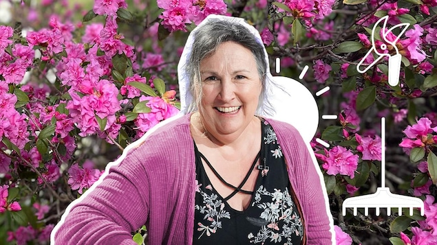 La femme pose sur un fond de fleurs roses.