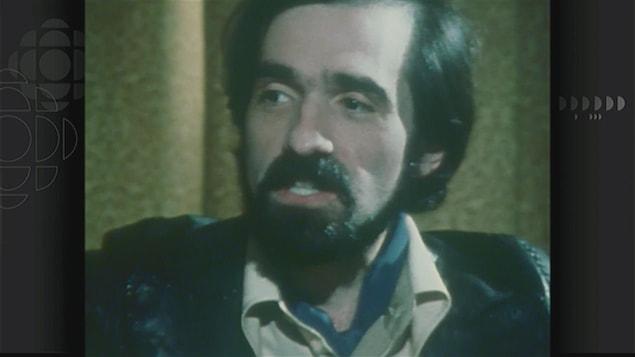 Un homme (Martin Scorsese) jeune, portant moustache et barbe, dans les années 70, en gros plan.