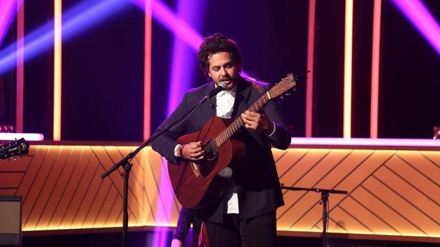 Il chante en s'accompagnant à la guitare
