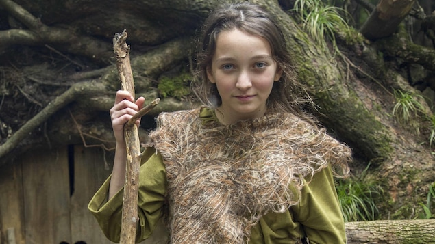 La jeune comédienne devant uen maison de lutins dans la fôret