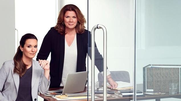 Les deux femmes sont dans un bureau vitré avec des piles de documents d'enquête.