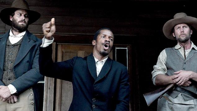 Un homme noir entouré de deux hommes blancs livre un discours.