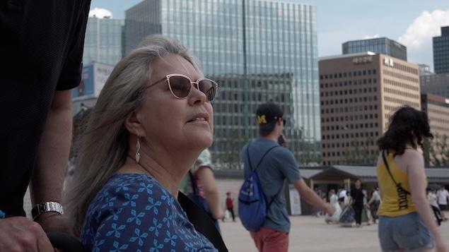 Une femme aux cheveux blonds qui porte des lunettes de soleil.