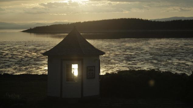Une cabane devant une étendue d'eau.