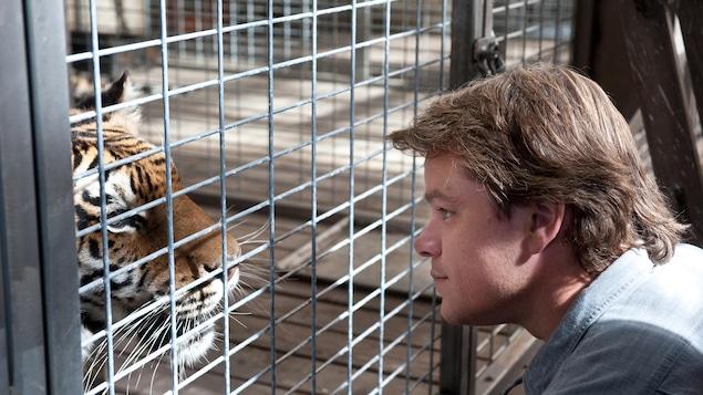 Un homme face à un tigre dans une cage.