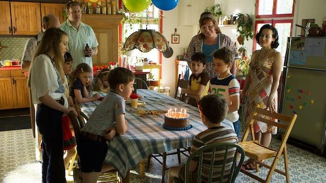 Un petit garçon s'apprête à souffler les bougies de son gâteau d'anniversaire.