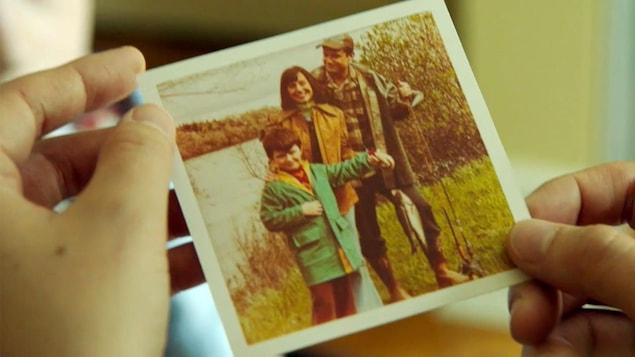 Une personne tient une photo de famille.