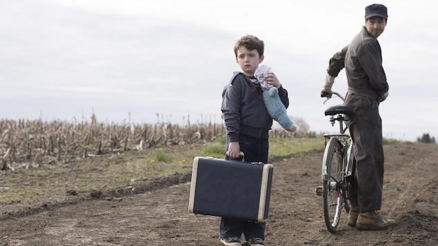 Sur un chemin de terre, un petit garçon tient sa valise et une peluche.