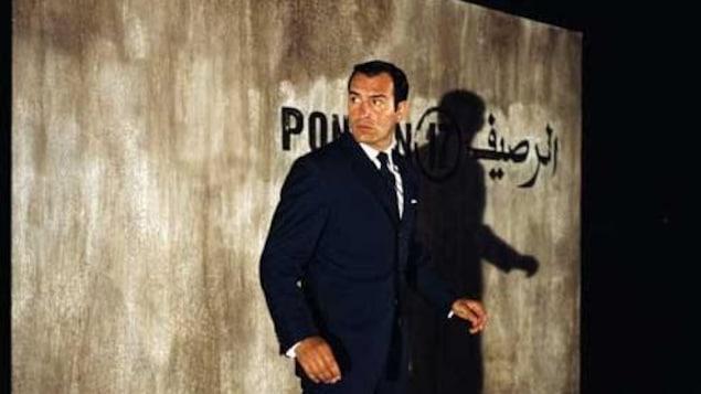 Un homme devant un mur où apparaissent des mots en français et en arabe.