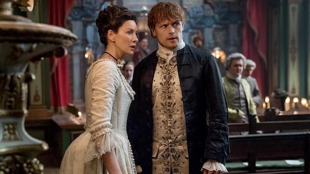 Les deux personnages se tiennent debout dans une église. Ils sont magnifiquement vêtus.