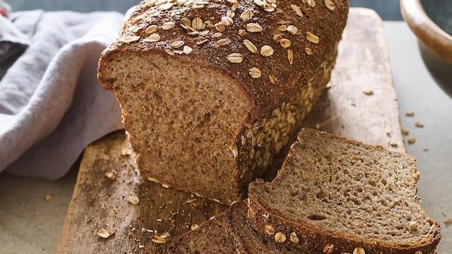 Le pain est posé sur une planche en bois. Quelques tranches sont coupées.