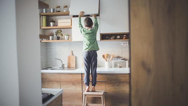 Un petit garçon seul à la maison fouille dans un placard de cuisine.