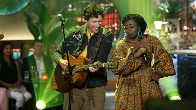 Patrice joue de la guitare et Djely danse en chantant.