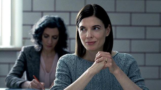 Une femme au premier plan, les mains croisées, devant une autre femme qui prend des notes.