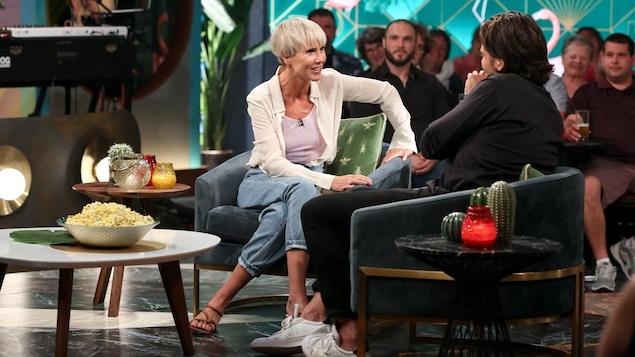 Elle est assise dans la partie « salon  » de l'émission. Elle porte un jeans, une camisole et une chemise blanche.