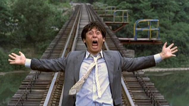 Un homme en costume cravate crie, les bras écartés, sur un rail de train
