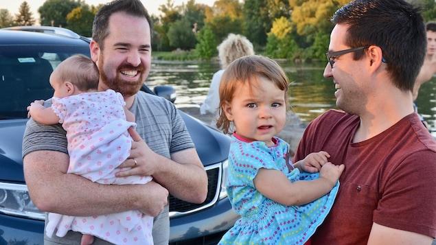 Les pères tiennent leurs bébés dans leurs bras.