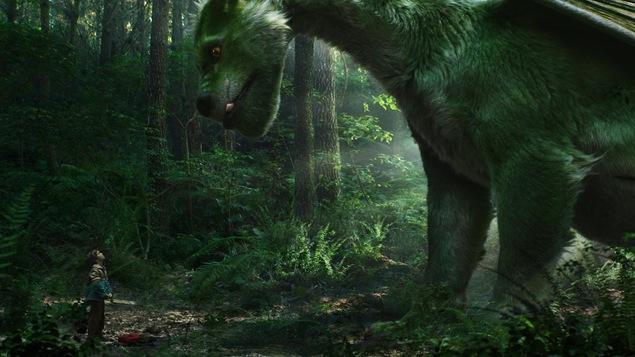 Un immense dragon vert devant un petit garçon, dans une forêt.