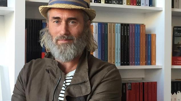 L'acteur Roy Dupuis, un chapeau sur la tête, et une barbe blanche