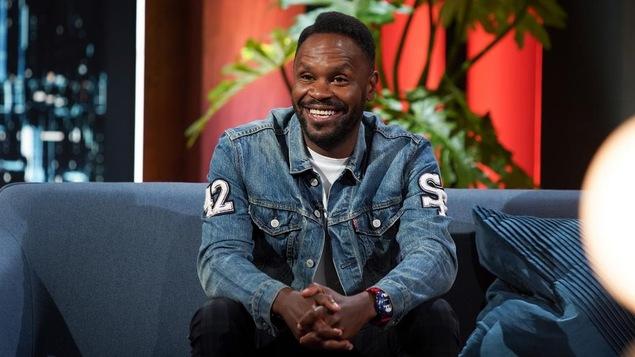 Un homme qui porte un t-shirt blanc et une veste en jean.