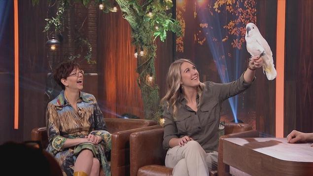 L'animatrice Chantal Lamarre et la biologiste Joanie Asselin regardent un cacatoès qui est perché sur le bras de la scientifique.