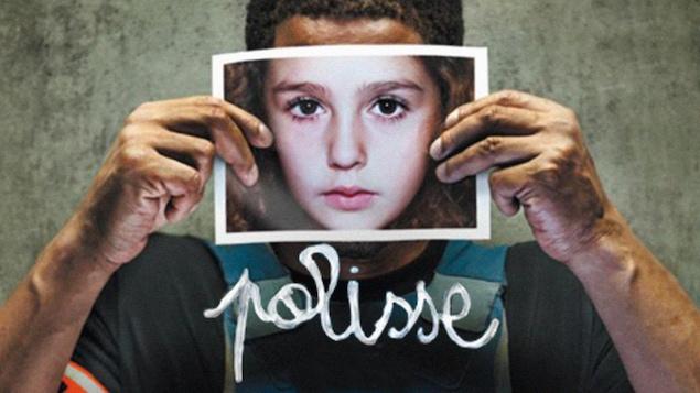 Un homme tient la photo d'un enfant devant son visage.