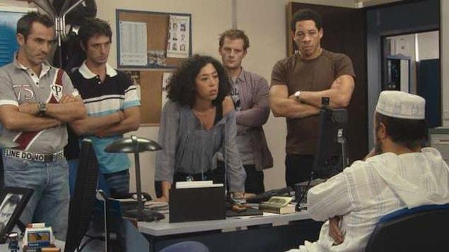 Cinq policiers debout derrière un bureau face à un homme assis.