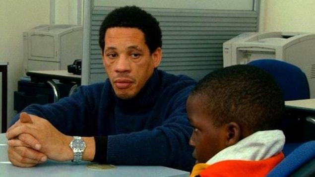 Un homme en pull bleu assis à côté d'un petit enfant.