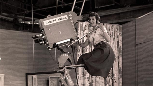 Une femme est tout en haut d'une grue où se trouve la caméra. Elle porte une jupe et des talons hauts ainsi que des écouteurs.