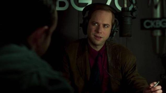 Un homme (Denis Bouchard) en studio, avec un casque sur les oreilles, devant un micro.
