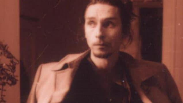 Une photo sépia d'un jeune homme.