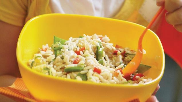 Un bol de riz dans les mains d'une femme.