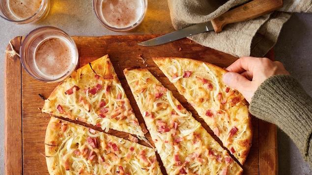 Une tarte qui ressemble à une pizza, sur une planche de bois avec trois bières et un couteau.