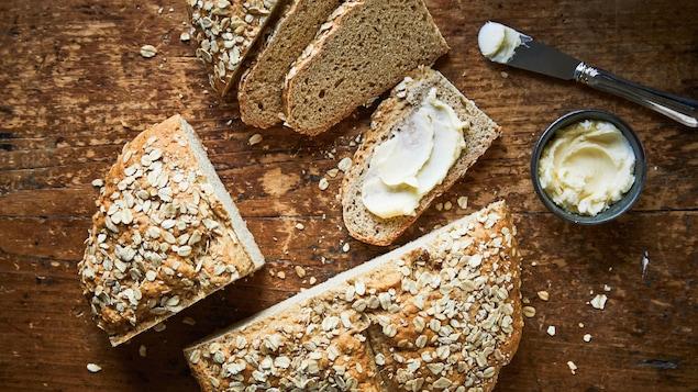Une miche de pain décorée d'avoine est tranchée sur une planche de bois avec un peu de beurre dans un ramequin.