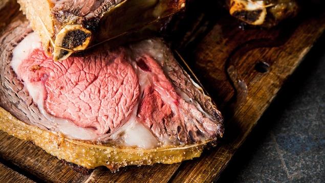 Une planche de bois avec des tranches de rôti de côtes de bœuf au jus et un bol de crème de raifort.