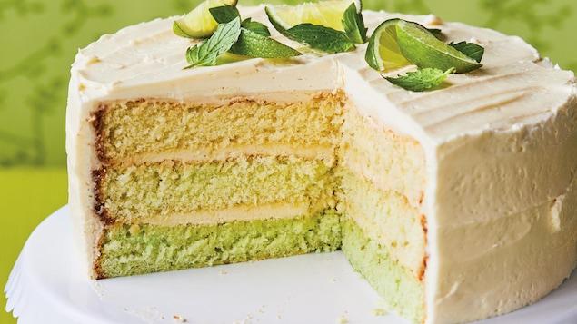 Le trois quart du gâteau vert à la lime sur une cloche à gâteau.