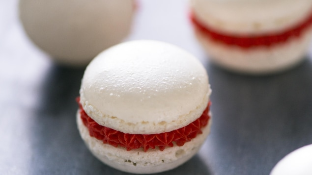 Gros plan de trois macarons aux couleurs de la Saint-Valentin sont sur un comptoir.