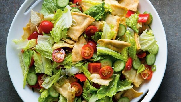 Un gros bol de salade fattouche avec des morceaux de pain pita un peu partout dans la salade.
